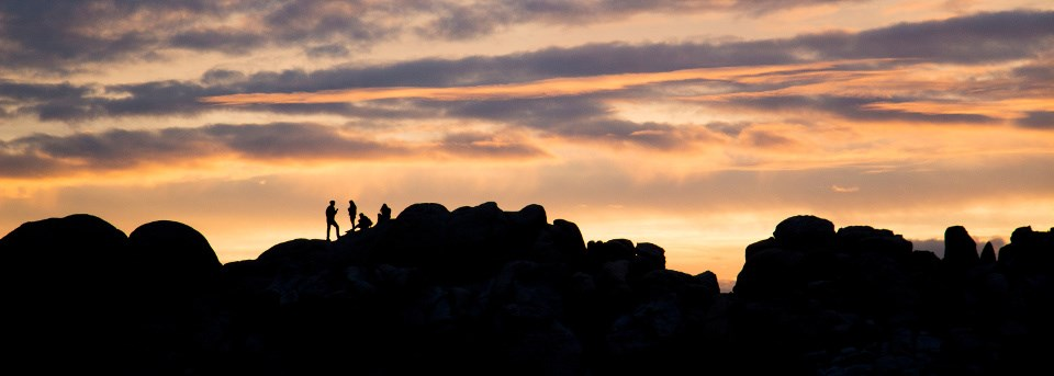 Five people silhouetted on a rocky outcrop at sunset