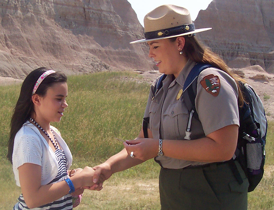 Teacher Ranger Jessica Dux awards a junior ranger badge.