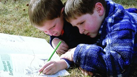 Two children working on activities in a Junior Ranger book