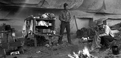 men near a campfire and wooden shelves