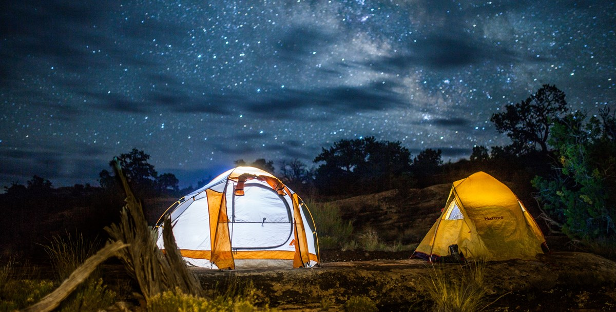 Two tents are illuminated under the night sky in the backcountry of Canyonlands