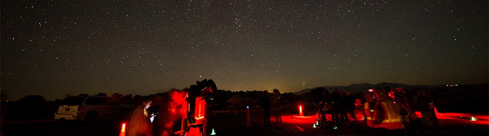people and telescopes illuminated in red with a starry sky overhead