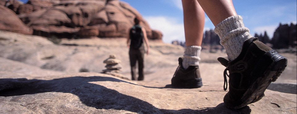 Two hikers walk away from the camera on a slickrock surface