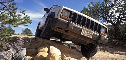 a jeep driving over a pile of rocks