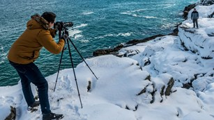 Photographer snaps photo of man standing in snow along coastline