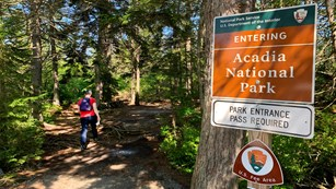 Visitor hikes on a trail past a park boundary and entry pass sign