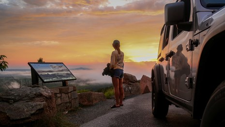 Woman watches sunset in a roadside pull out standing between a jeep and a park wayside sign.