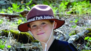 A Junior Ranger proudly wearing a Junior Ranger hat