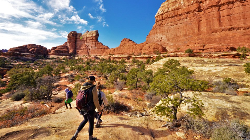 three hikers on smooth sandstone in front of looming red cliffs