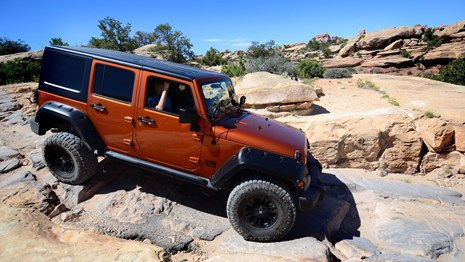 an orange Jeep driving over a steep, rocky surface