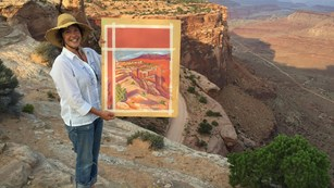 a woman at a scenic overlook holds up a painting