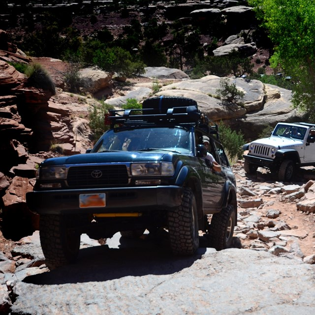 A blue SUV drives up a rocky slope