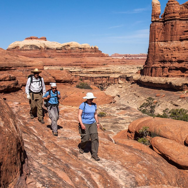 three people walk on red slickrock