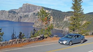 A blue car travels along the East Rim Drive.