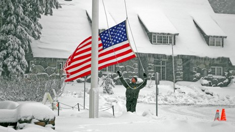 A ranger raises the US flag in a snowstorm.