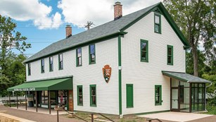 A photo of the exterior of Boston Mill Visitor Center, a white building with green trim