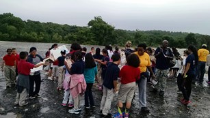A group of young students and adults stand near a river on a cloudy day.