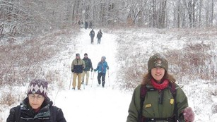 Ranger and visitors on a trail covered in snow