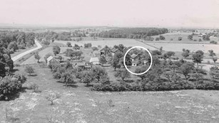 A black and white photo shows the Warfield house property in the early 1900s.