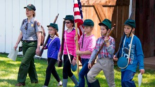 A park ranger marches with students at one of the historic homes on the battlefield.