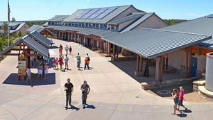 Several people walk through Visitor Center Plaza: outdoor displays on the left, building on right