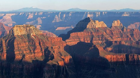 Landscape seen from Grand Canyon Lodge. Two massive reddish peaks at sunset.