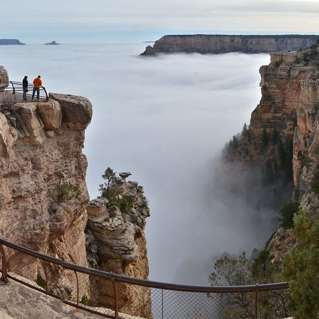 Clouds entirely filling Grand Canyon, on right, atop a massive stone pillar, two tiny people