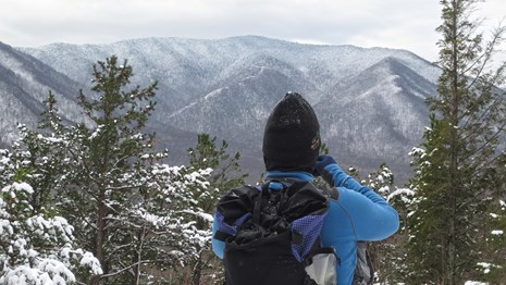 A hiker stands looking at snow-covered mountains.