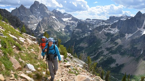 Two backpackers climbing a trail in the Teton Range with the Grand Teton in the distance.