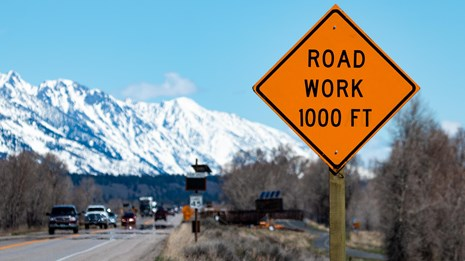 Road Work 1000ft orange sign with mountains in the background