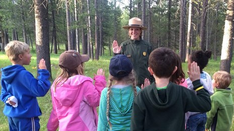 Kids getting sworn in as junior rangers by a park ranger