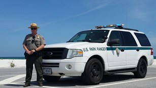 A park ranger stands in front of a patrol SUV just in front of a beach.