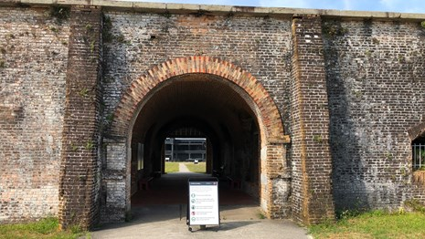 A safety poster sites at the arched entrance to a masonry fort.