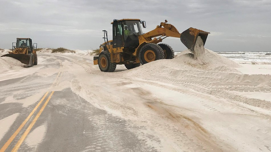 Two heavy machines clear sand from a two lane road.