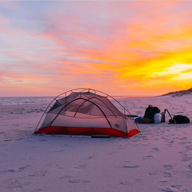 A tent is set up on a beach with the sun setting in the background.