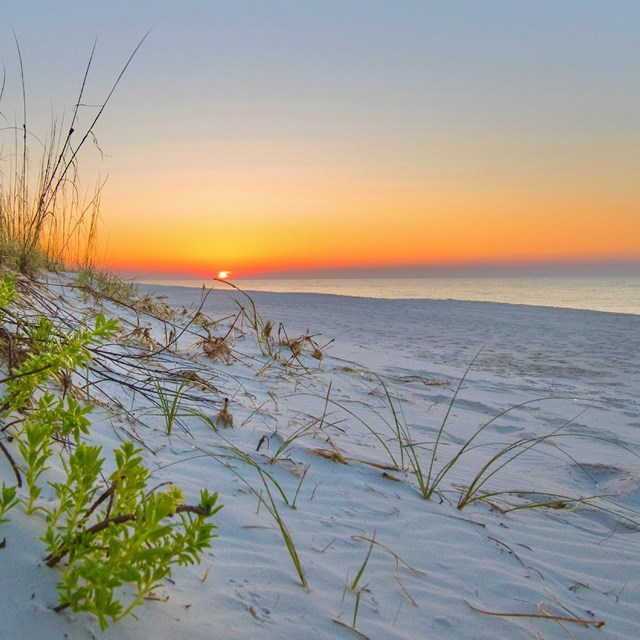 The sunrises over a white sand beach.