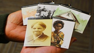 A woman's hands holding five Harriet Tubman collective trading cards