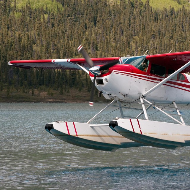 A red and white floatplane takes off from a lake