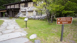 A sign next to a path leading to a rustic building reads
