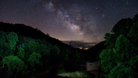 starry sky shines over orange sunset with green trees and river below