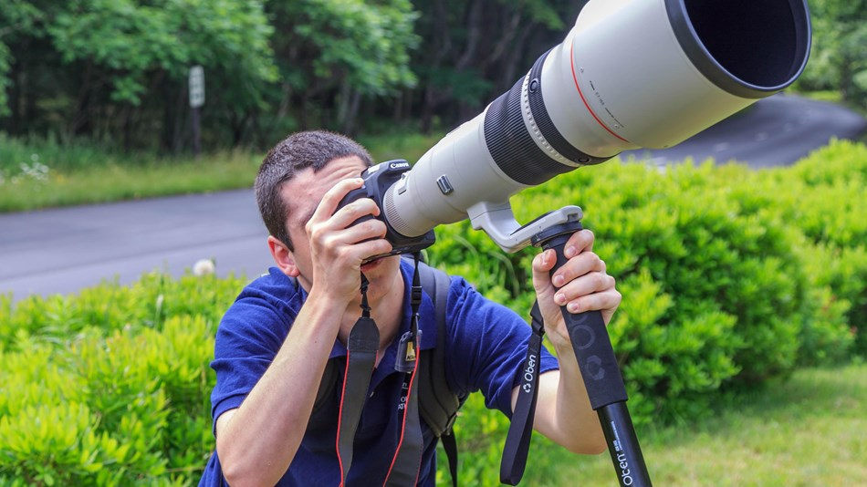 Man looking through camera with very large lens