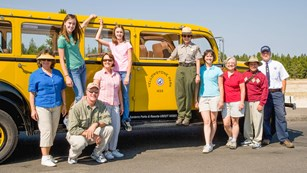 Photo of park and partner employees alongside an historic Yellow Bus