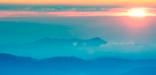 Image of beautiful sunrise over blue misty mountains.