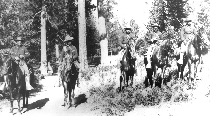 photo of African-American soldiers on horseback in a grove of trees