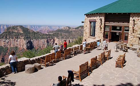Canyon-facing patio patio of Grand Canyon Lodge. Several people are sitting in chairs enjoying the view.