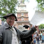 Man in 18th-Century costume holding up a copy of the Declaration of Independence behind Independence Hall.