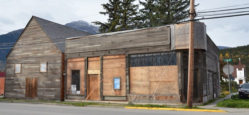Two wooden buildings in states of repair