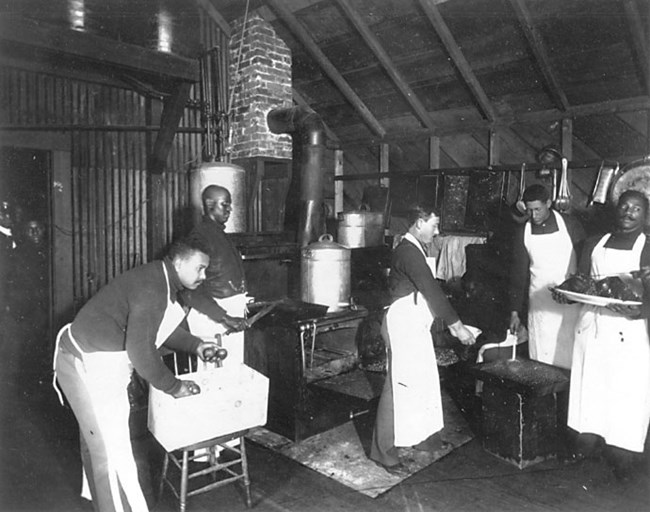 Historic photo of five men in aprons in a kitchen