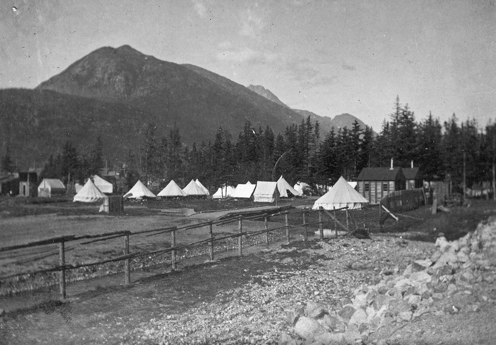 White tents in cleared area with cabins, trees, and mountain backdrop.