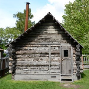 Log cabin with metal stovepipe.